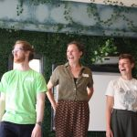 Artists laughing at a training event, in front of a wall covered in greenery.