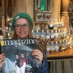 Volunteer holding a copy of a magazine in which she was featured, in front of apothecary bottles on the counter.