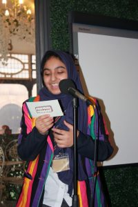 Astrea Academy student reading from a card labelled Bourbon biscuit