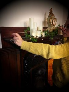 Shop elf measuring the length of the fireplace with string.