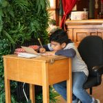 Child sat at a desk next to a wall covered in greenery, looking at his notebook, writing.