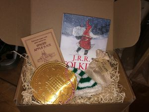 Gift box containing book, elf hat, candy canes and gold coin.