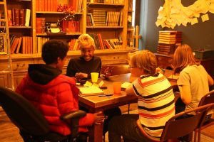 Artist Sile Sibanda with three young people, sat round a table.